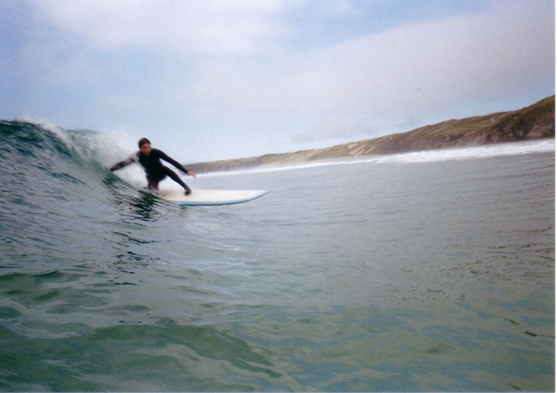 A surfer on a wave. He's crouching, touching the wave with his hand as the wave breaks. The wave is chest high, blue-green color. There are brown-green hills in the background on the land.